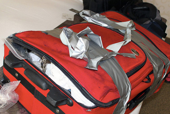 fully packed open suitcase wrapped with duct tape